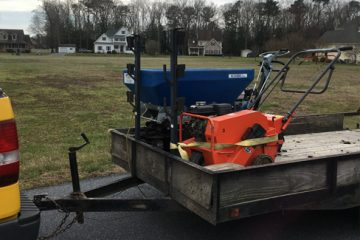 A trailer with mower and spreader in front of a large yard