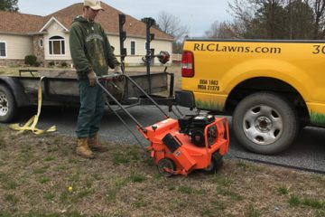 A man pushing an orange lawn mower