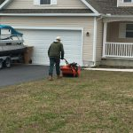A person pushing a mower in front of a house