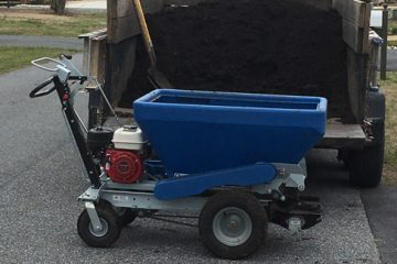 A blue mulching and fertilization spreader being filled with mulch