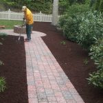 A person taking care of the newly placed mulch