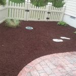 A yard with new red and brown mulch
