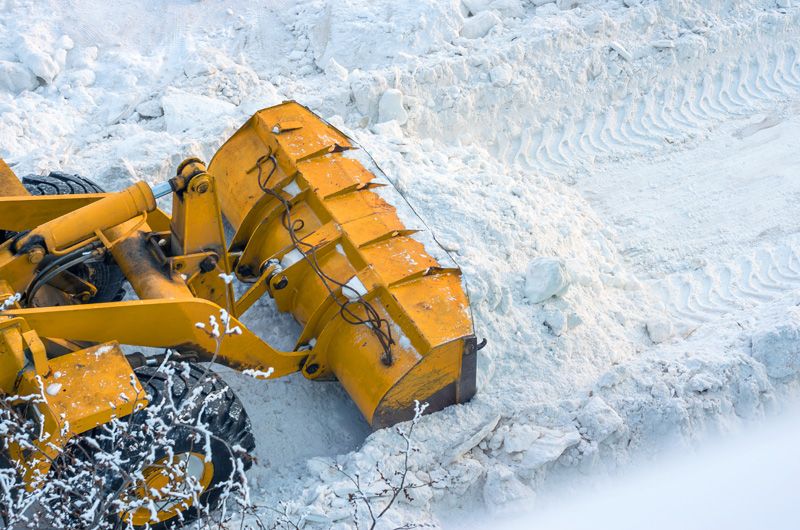 A bulldozer pushing and shoveling snow off of a pathway