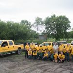 A group photo of 17 people and the vehicles of Royal Lawn Care & Landscaping