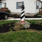 A model lighthouse stands in the middle of a newly mulched yard
